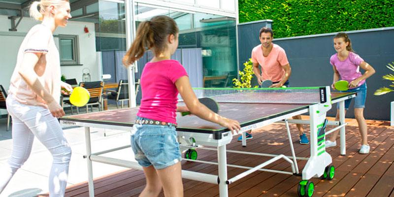 familia jugando al ping pong en el jardín