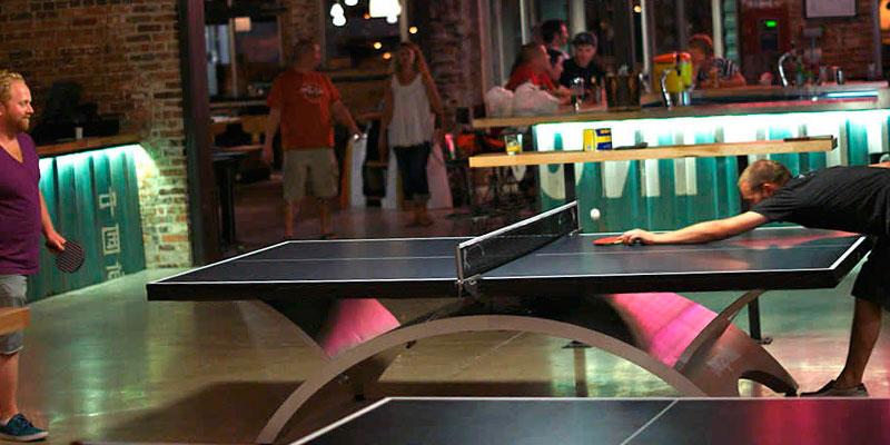 derrotado jugando al ping pong en un pub
