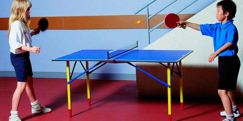 niños jugando en mesa ping pong infantil